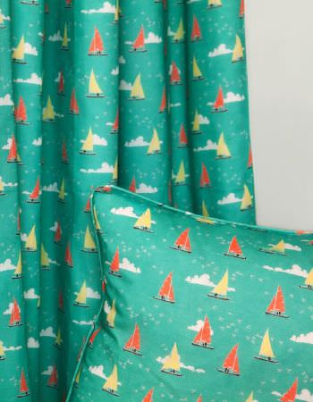 Emily Burningham -  Emily Burningham Fabric Collection - Curtains in sea green depicting sailing boats with orange and yellow sails and matching cushion with piped edging.