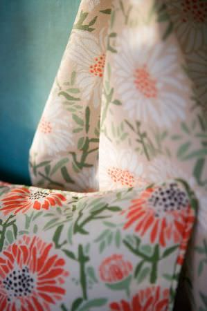 Emily Burningham -  Emily Burningham Fabric Collection - Fabric with pale peach-pink background with large white daisy-type flowers and light green foliage. Matching cushion with piped edging.