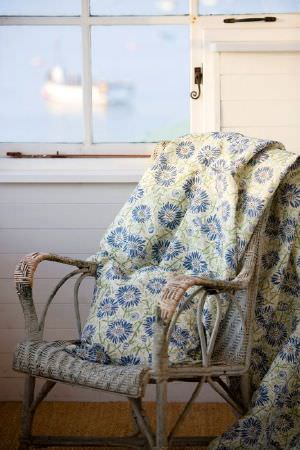 Emily Burningham -  Emily Burningham Fabric Collection - Light beige fabric decorated with a pattern featuring vibrant blue flowers with green stems