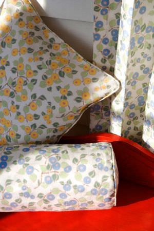 Emily Burningham -  Emily Burningham Fabric Collection - White cushion with a pattern of yellow berries and a matching pattern of blueberries on a curtain and another cushion