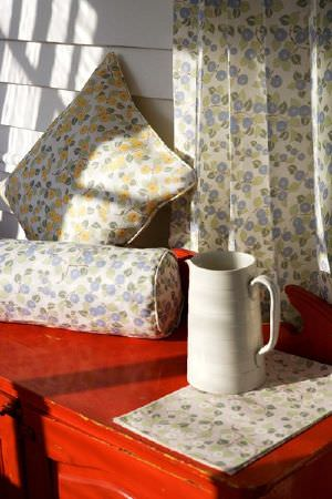 Emily Burningham -  Emily Burningham Fabric Collection - Matching pattern featuring colourful berries on white cushions, curtain and a fabric sample