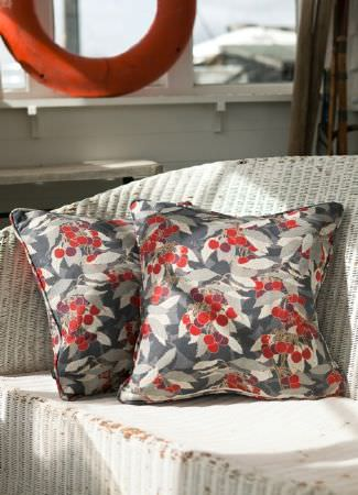 Emily Burningham -  Emily Burningham Fabric Collection - Interesting woven sofa covered with a set of dark grey cushions featuring a vibrant pattern of cherries