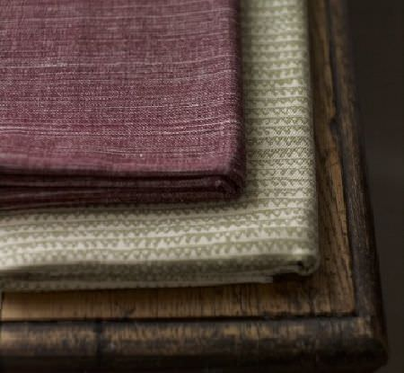 Fermoie -  Fermoie Fabric Collection - A fold of burgundy coloured fabric lying on a fold of cream-beige triangle print fabric, lying on a rustic wood table