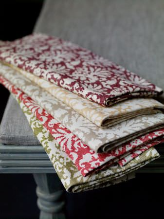 Fermoie -  Fermoie Fabric Collection - A grey table with folds of ornately patterned fabric in white, green, red, grey, gold and burgundy