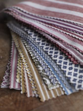 Fermoie -  Fermoie Fabric Collection - Swatches of various different striped and patterned fabrics in shades of white, purple, gold, brown, blue and dark red