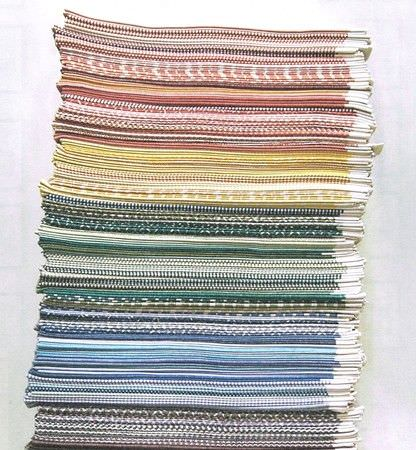 Fermoie -  Fermoie Fabric Collection - A tall stack of folded fabrics featuring various different patterns in purple, blue, green, yellow, red and orange shades