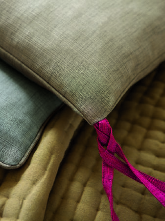 Fibre Naturelle -  Aspen Fabric Collection - Pale mustard furry quilt. Pale sage green piped edged cushion with slubbed effect pattern and deep pink ties. Similar pale blue cushion.