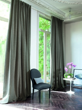 Fibre Naturelle -  Aspen Fabric Collection - Pale sage green curtains, chair in grey fabric with small white cushion.