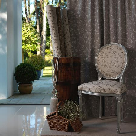 Fibre Naturelle -  Bella Fabric Collection - Beige upholstered chair and a collection of beige and brown fabrics decorated with the same floral pattern