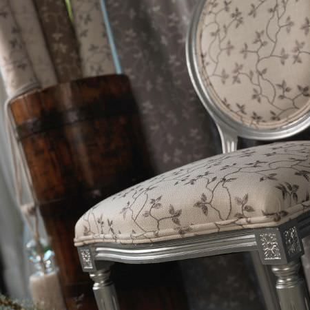 Fibre Naturelle -  Bella Fabric Collection - Upholstered beige chair featuring a brown floral pattern and a silver frame with a set of fabrics in the background