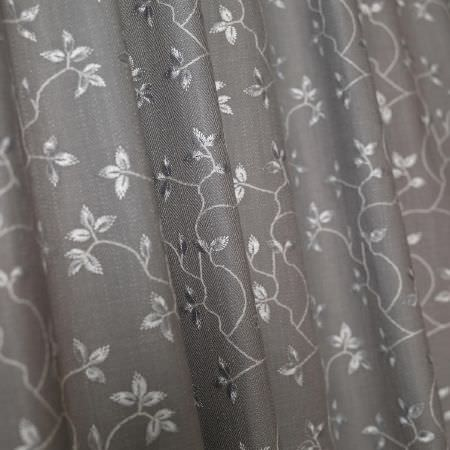 Fibre Naturelle -  Bella Fabric Collection - Close-up view of a dark grey curtain decorated with threaded floral pattern in colour silver