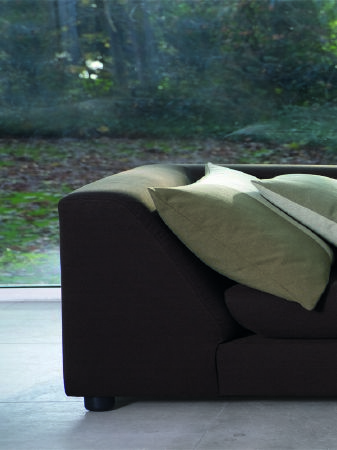 Fibre Naturelle -  Boston Fabric Collection - Low, dark grey coloured sofa which has a wide, sloping armrest, with a couple of large, square, light green and cream coloured cushions