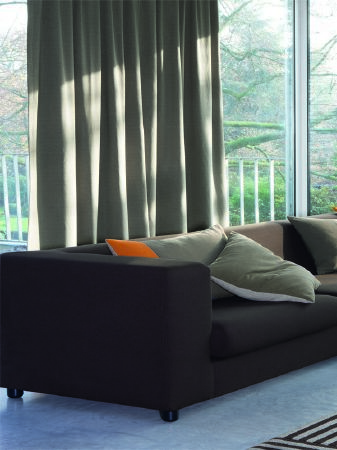 Fibre Naturelle -  Boston Fabric Collection - Grey sofa which is very large and low with green, cream and orange scatter cushions, in front of long, plain green-grey curtains, with a rug