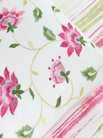 Fibre Naturelle -  Botanics Fabric Collection - Pink, white and green striped fabric beneath a floral cushion with a bright pink and green design on a white background