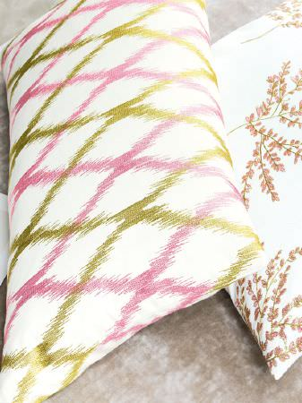 Fibre Naturelle -  Botanics Fabric Collection - A rectangular pink, green and white patterned cushion next to a white cushion with a tree print in green and pink shades
