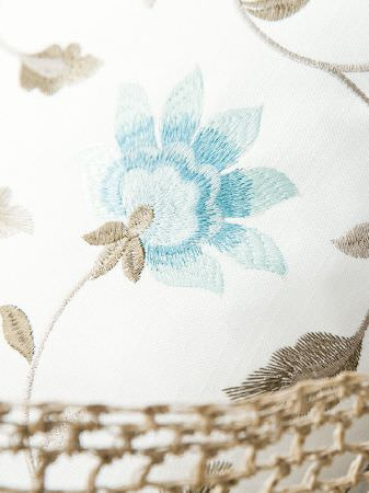 Fibre Naturelle -  Botanics Fabric Collection - Stylised flowers embroidered in sky blue shades with leaves and stems in light brown shades on a white fabric background