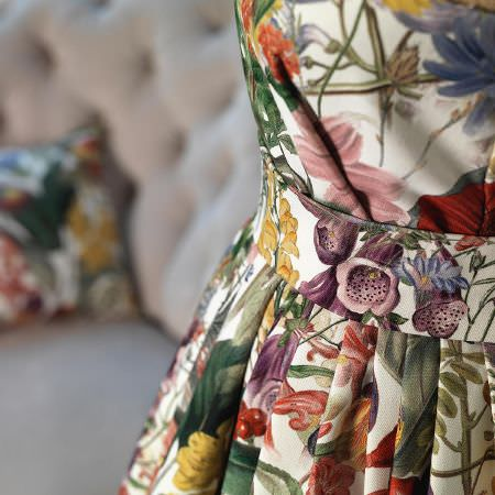 Fibre Naturelle -  Chelsea Fabric Collection - A close-up view of an elegant white dress from the Chelsea Fabric Collection decorated with vibrant floral pattern