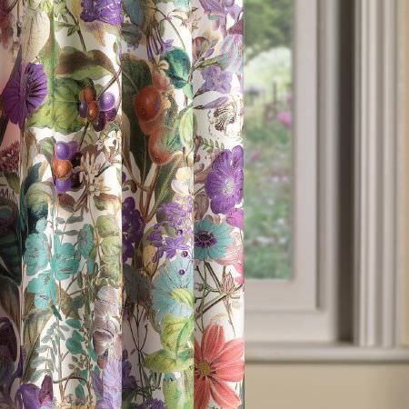 Fibre Naturelle -  Chelsea Fabric Collection - A close-up view of a curtain dyed in light beige decorated with a dominant pattern of colourful flowers