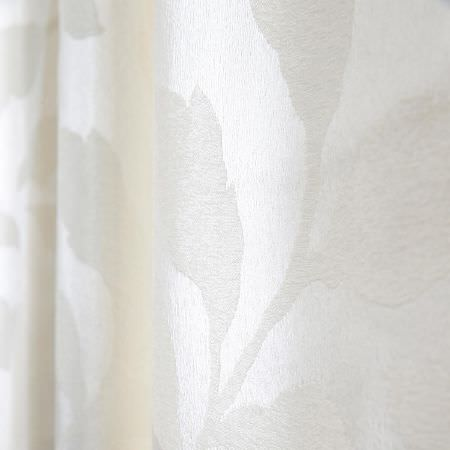 Fibre Naturelle -  Epsom Fabric Collection - A close-up view of a curtain dyed in white decorated with barely noticeable white floral pattern