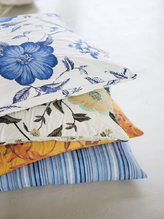 Fibre Naturelle -  Florence Fabric Collection - Four cushions: blue and white floral, white, black and gold floral, burnt orange leaf print, and blue and white striped