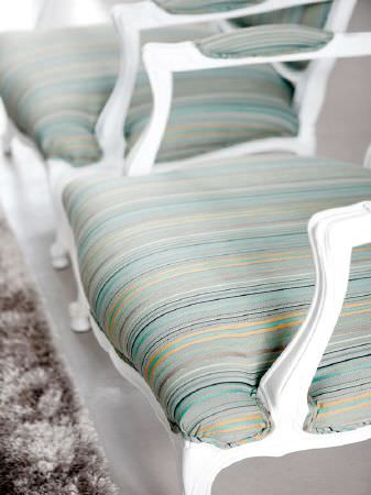 Fibre Naturelle -  Florence Fabric Collection - Carved wooden white armchairs with grey, turquoise and gold striped seats and armrests, next to a fluffy grey rug