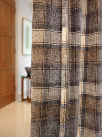 Fibre Naturelle -  Glencoe Fabric Collection - Checked curtains in cream, brown and dark grey, draped in front of a wooden door, occasional table, black vase and picture