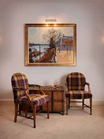 Fibre Naturelle -  Glencoe Fabric Collection - A large framed painting with two dark checked fabric armchairs with wooden frames, with a wooden chest style side table