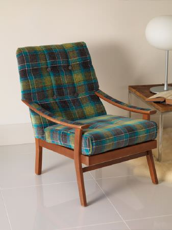Fibre Naturelle -  Glencoe Fabric Collection - Wood and metal table with a white domed lamp and a book beside an armchair with a wood frame and a tartan seat and back