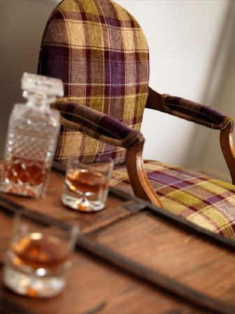 Fibre Naturelle -  Glencoe Fabric Collection - Cream, green and purple checked wooden framed armchair beside a wooden table with a cut glass decanter and two glasses