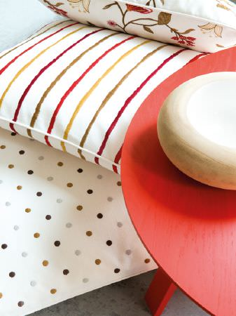 Fibre Naturelle -  Henley Fabric Collection - Round red table beside white cushions with grey and brown dots, red, gold and green stripes, and red, gold and green florals