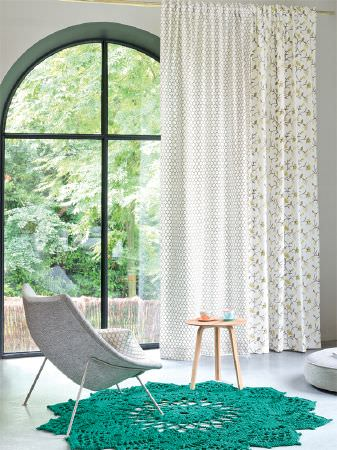 Fibre Naturelle -  Henley Fabric Collection - Turquoise crocheted rug with a light grey tub chair, small wood table and white curtains with two grey-green patterns