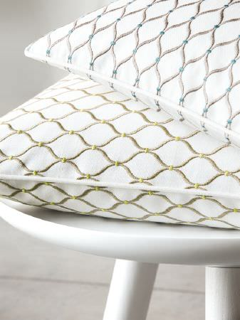 Fibre Naturelle -  Henley Fabric Collection - Olive green wavy lines patterning a white cushion, beneath a white cushion with grey wavy lines, on a small white stool