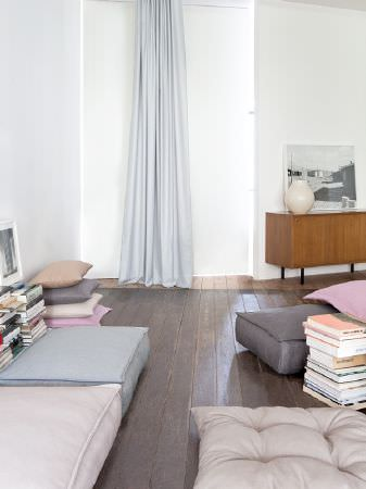 Fibre Naturelle -  Kingsley Fabric Collection - Large floor cushions in pale colours, stacks of square cushions, piles of books, a wooden side table and light curtains