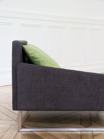 Fibre Naturelle -  Madison Fabric Collection - Side view of a simple plain dark grey sofa with sloping armrests and a metal base, with a plain lime green scatter cushion