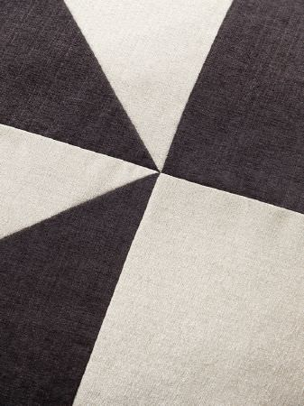 Fibre Naturelle -  Madison Fabric Collection - Large triangles and squares stitched together into a geometric design using fabrics in plain charcoal and grey-white