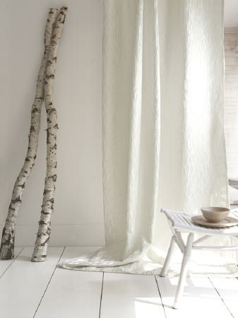 Fibre Naturelle -  Metalix Fabric Collection - White textured fabric, beside a small folding white table and beige crockery