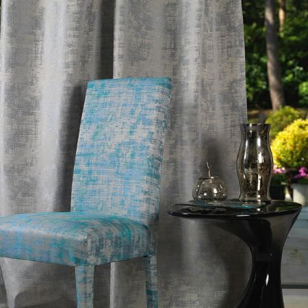 Fibre Naturelle -  Miami Fabric Collection - Light grey curtain and a vibrant blue upholstered chair decorated with the same conventional design