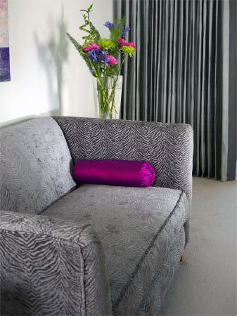 Fibre Naturelle -  Milano Fabric Collection - Silver textured fabric sofa with magenta bolster cushion, to a tall glass vase and plain floor-length grey curtains