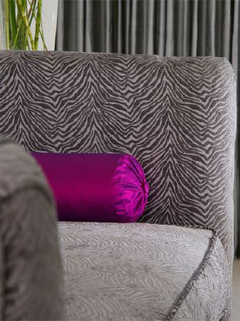 Fibre Naturelle -  Milano Fabric Collection - Satin effect magenta bolster cushion on an animal stripe sofa, with grey curtains