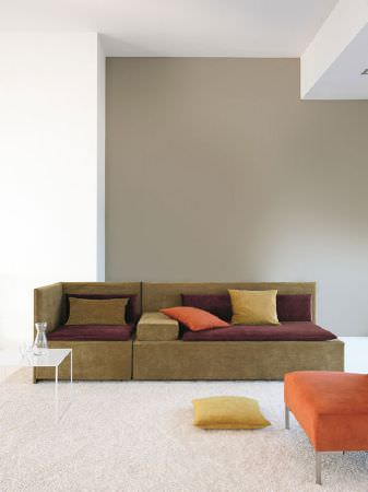 Fibre Naturelle -  Monza Fabric Collection - Square green sofa with aubergine back/seat cushions, cushions in green, yellow and orange, an orange footstool and a vase on a white table