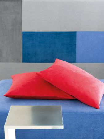 Fibre Naturelle -  Monza Fabric Collection - Bright red suede effect cushions on a cobalt blue seat, beside an angular silver table