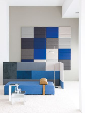 Fibre Naturelle -  Monza Fabric Collection - Blue, grey and white wall panel with a matching low screen, a white floor lamp, a blue and gold seat, two metal tables and glass vases