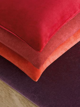 Fibre Naturelle -  Monza Fabric Collection - Olive green and aubergine coloured base, with a stack of orange, terracotta and red cushions