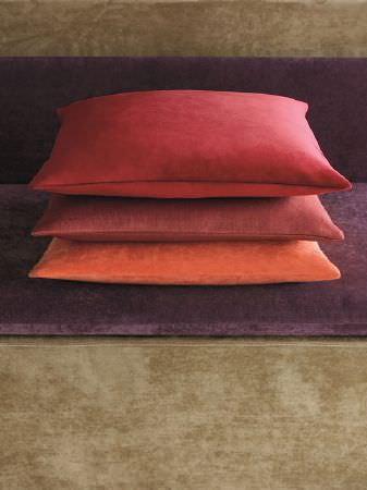 Fibre Naturelle -  Monza Fabric Collection - Red, terracotta and orange cushions stacked on a purple and green sofa