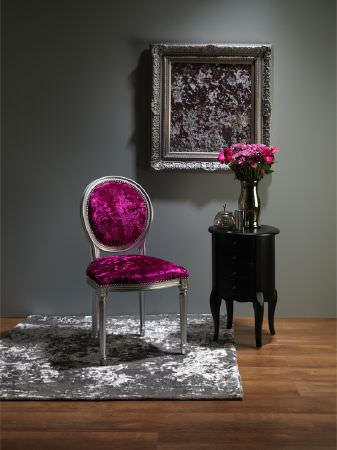 Fibre Naturelle -  Panther Fabric Collection - Velour magenta armchair with silver frame, a textured silver rug, black table with drawers, silver mirror and chrome vase