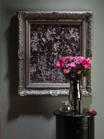 Fibre Naturelle -  Panther Fabric Collection - An ornate square silver picture frame, a small black table with drawers, flowers and a chrome coloured vase and accessories