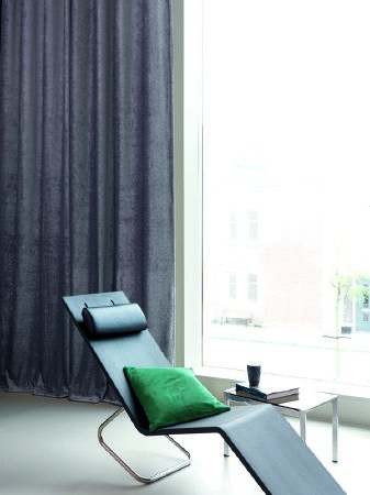 Fibre Naturelle -  Paris Fabric Collection - Black minimalist reclining chair with a green cushion, small side table, and long, dark grey curtains