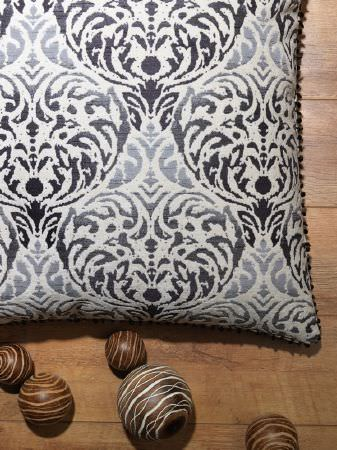 Fibre Naturelle -  Safari Fabric Collection - Patterned wooden spheres scattered next to a white square cushion featuring a dark black and grey coloured ornate pattern