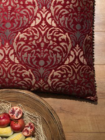 Fibre Naturelle -  Safari Fabric Collection - Luxurious scatter cushion covered with an ornate deep red and gold pattern, beside a wooden bowl filled with corn and fruit