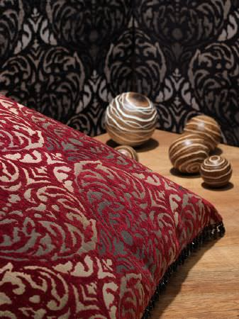 Fibre Naturelle -  Safari Fabric Collection - An ornate pattern covering a deep red and gold scatter cushion and a folding black and grey screen, beside five wooden spheres